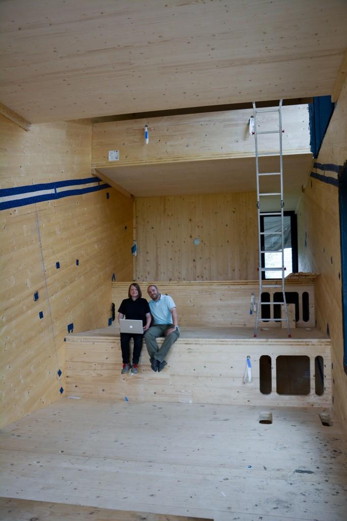 """Die Architektin, Innenarchitektin und Tischlerin Henrike Gänß arbeitet seit zwei Jahren an dem Mini-Max Projekt. Unterstützt wird sie von ihrem Projektpartner, dem Wirtschaftsingenieur Marc Rother. Mit ihrem Büro für Konzeption und Gestaltung, HOCH5, wollen die beiden ihre Visionen aus dem Studium in der Realität umsetzen. """"Zum einen wird Wohnraum immer knapper, zum Beispiel in den Großstädten. Andererseits wird Wohnraum auch immer aufgeblasener und minderwertiger. Das hat zur Folge, dass die Menschen auch immer mehr Wohngiften ausgesetzt sind. Wir wollen zeigen, dass es ein Ausweg gibt. Das Mini-Max-Projekt beweist, dass man Raum reduzieren kann, ohne dass man das Gefühl von Verzicht hat"""", sagt Henrike Gänß. Mini-Max ist noch in der Bauphase – im Juli 2014 haben Gänß und Rother den Rohbau abgeschlossen. Hier sitzen die Ingenieure in dem künftigen Einraum bei einer Baubesprechung. Von der Fläche her umfasst diese Funktionszone neun Quadratmeter."""