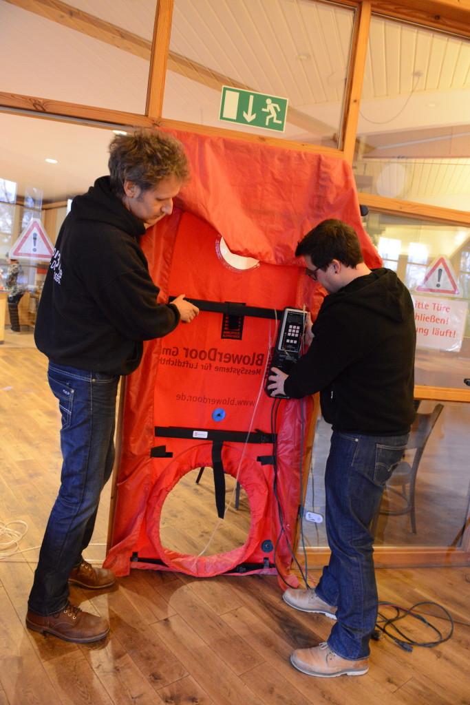 Referent Holger Merkel (links) mit Architekt Dennis Krupp: Die Teilnehmer lernen beim BlowerDoor- Basisseminar, wie das Equipment auf- und abgebaut wird.