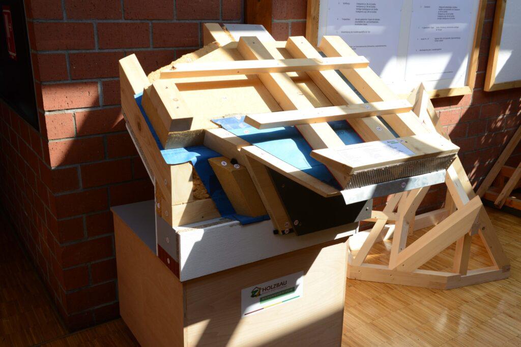 """Dachsanierungs-Eckmodell des Bildungszentrums Holzbau in Biberach: Das dreidimensional angeordnete Modell weist vor allem auf die Anschlusssituation zwischen Traufe und Ortgang. Als Beispiel wird hier gezeigt, wie die luftdichte Ebene über den Sparren geführt wird, indem der Dachvorsprung vorher abgeschnittten wurde. """"So kann die Gebäudehülle komplett eingepackt werden, ohne Durchbrüche"""", sagt Zimmerermeister und Ausbilder Helmut Schuler. Der Dachvorsprung wird später an die Konterlatten gehängt."""