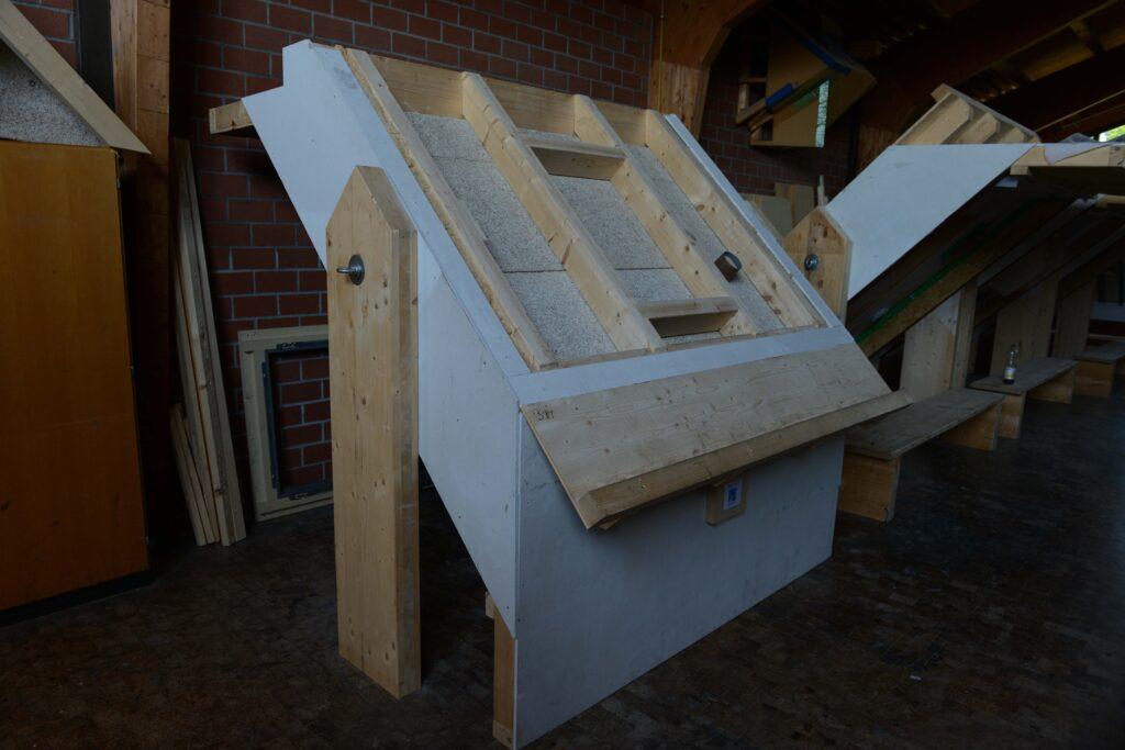 Das Schmettlingsmodell mit der Seite, die eine Dachsanierungssituation zeigt.