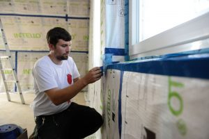 Carpenter uses adhesive tape to seal a building
